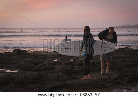 Surfers Surf On The Waves, Bright Sunset On The Coast, Tenerife, Canary Islands, Spain