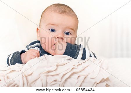 Cute happy baby boy with big blue eyes.