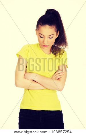 Unhappy teenage woman with crossed arms looking down.