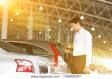 Indian business man at car park, holding car remote key.