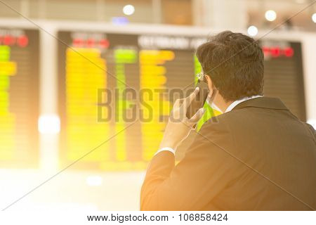 Asian Businessman looking at airport flight timetable and on the phone, filter sun.