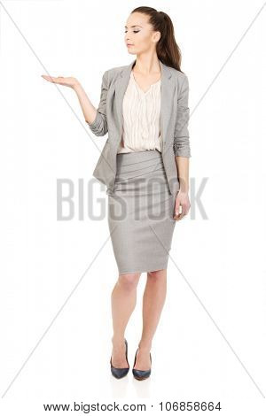 Businesswoman showing empty hand for product.