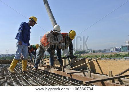 Construction Workers Using Concrete Hose from Concrete Pump