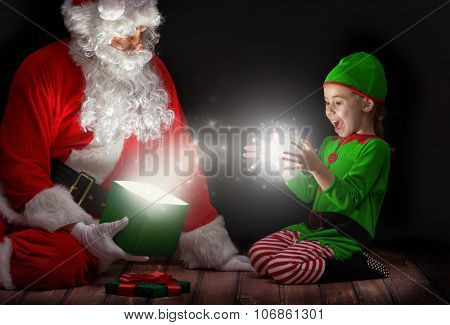 Cute little girl and Santa Claus opening a magic gift box.