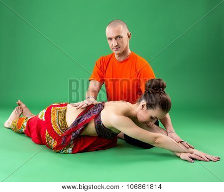 Yoga. Instructor helps woman to perform asana