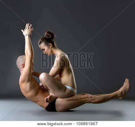 Studio photo of topless partners exercising yoga