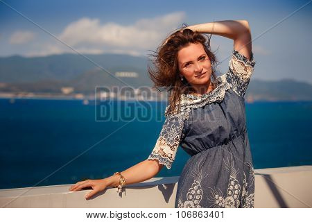 Brunette Girl In Short Grey Frock Leans On Wall Against Sea