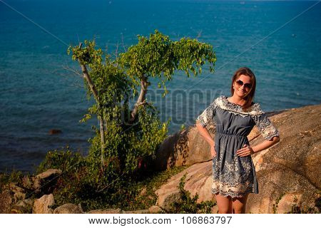 Brunette Girl In Grey Frock Stands On Rock Against Sea