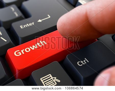 Pressing Red Button Growth on Black Keyboard.