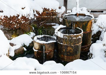 Wooden barrels filled with water and snow, close up details of old district at historical Takayama town in Japan on winter day