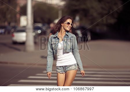 Beautiful young woman wearing sunglasses, jeans shorts and top walking on the street