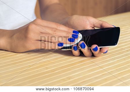 Female Hands With Blue Manicure Clean The Phone Display