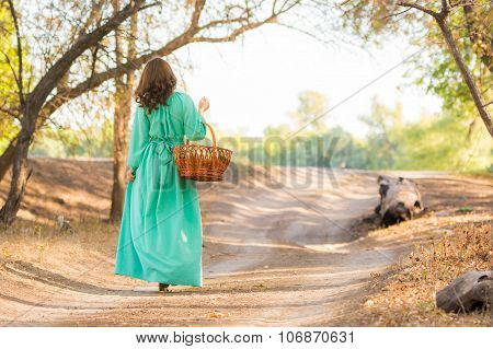 A Girl In A Long Dress Holding A Basket Is On The Road Into The Distance