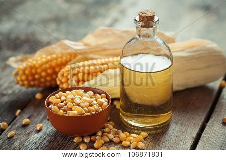 Corn Essential Oil Bottle, Seeds In Bowl And Corncobs On Kitchen Table.