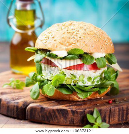 Vegetarian burger with egg and pea patty, fresh salad tomato.