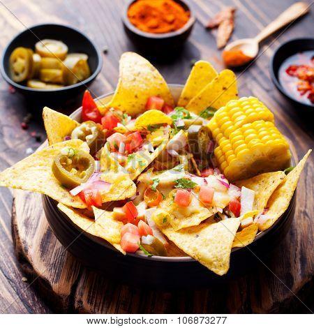 Tortilla nachos, cheese sauce, chicken, jalapeno, tomato, salsa, corn cobs.