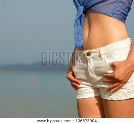 Part Of Woman Body In Shorts Against Sea.