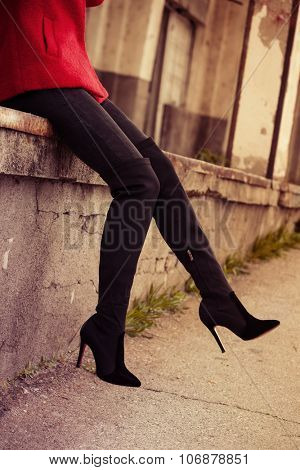 young woman in red short coat, pants and high heels boots,  outdoor on street, closeup