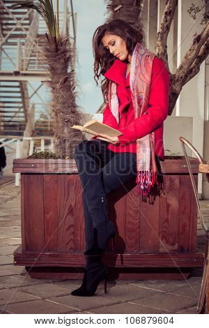 fashionable young woman stand outdoor by potted trees hold and read a book, outdoor shot, autumn day, full body shot