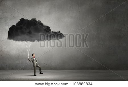 Young businessman caught black cloud with rope