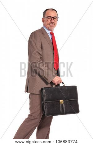 side view of a smiling old businessman with briefcase walking on white background