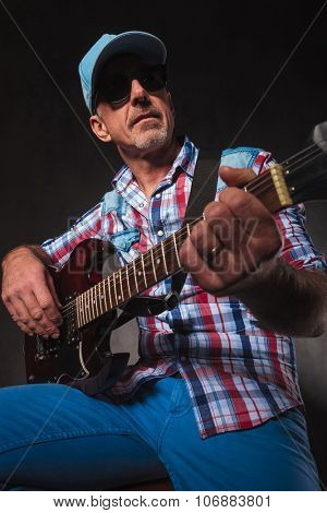 seated senior rocker playing electric guitar and looks away to a side in studio