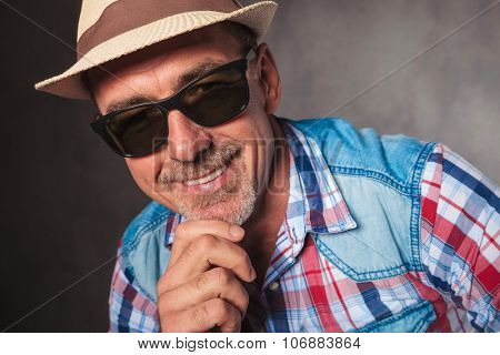 smiling senior casual man holding his chin and smiles to the camera, wearing a summer hat and sunglasses
