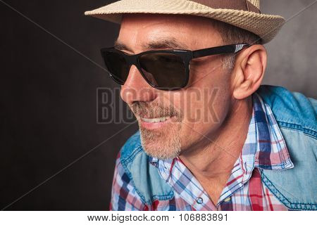 side profile picture of a happy mature man smiling , wearing summer hat and sunglasses in studio