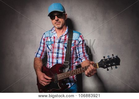 serious old guitarist playing his electric guitar while standing in studio wearing hat and sunglasses