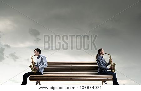 Duet of young man and woman musicians playing saxophones