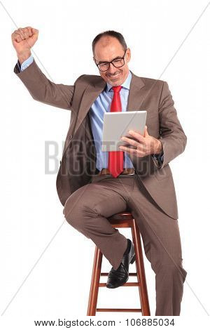old businessman reading good news on tablet pad computer, with hand up in the air, celebrating success