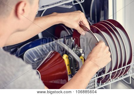 closeup of a young man introducing or taking out a plate into a dishwashing machine