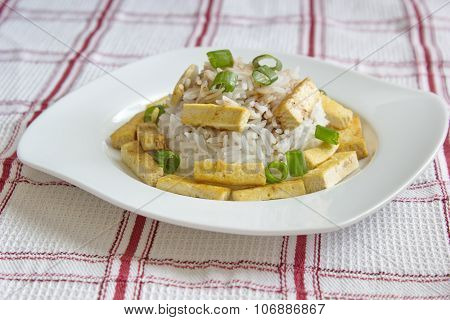basmati rice with roasted pieces of tofu served on chequered tablecloth