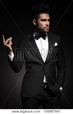 Handsome elegant business man looking away from the camera while snapping his fingers.