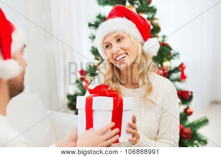 christmas, holidays and people concept - happy couple in santa hats with gift box sitting on sofa at home