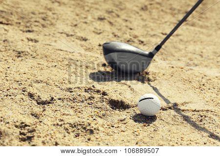 Golf club and ball on sandy golf course