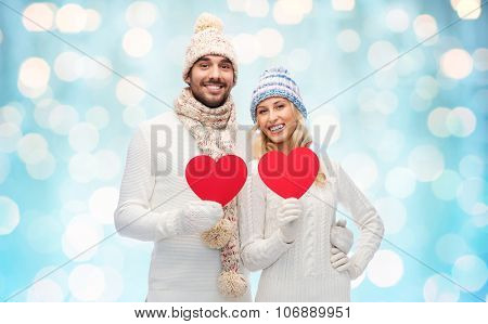 love, valentines day, couple, christmas and people concept - smiling man and woman in winter hats and scarf holding red paper heart shape over blue holidays lights background