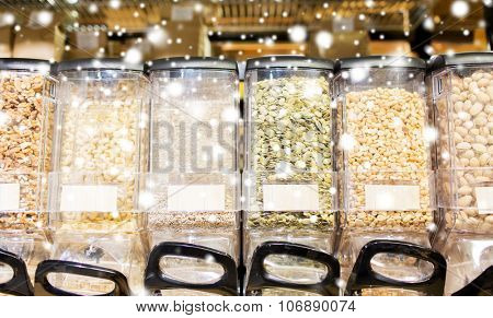 sale and eco food concept - row of jars with nuts and seeds at grocery store over snow effect