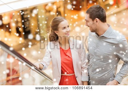 sale, consumerism and people concept - happy young couple with shopping bags rising on escalator and talking and raising on escalator in mall with snow effect