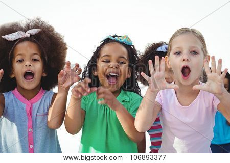 Scarey girls with hands raised against a white background