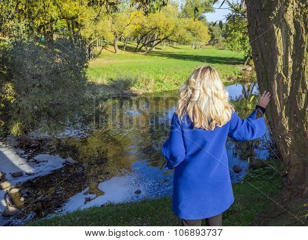 The Girl Was Standing On The Bank Of The River In The Park