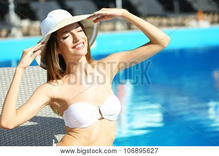 Young woman resting on sunbed at swimming pool