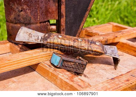 Old Smoker And Other Tool Of The Beekeeper On The Wooden Box.