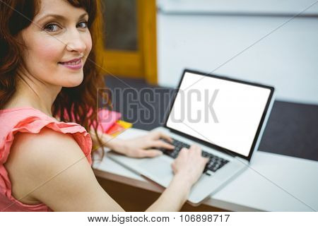 Mature student in lecture hall using laptop at the university