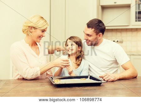 food, family, christmas, hapiness and people concept - happy family in making cookies at home