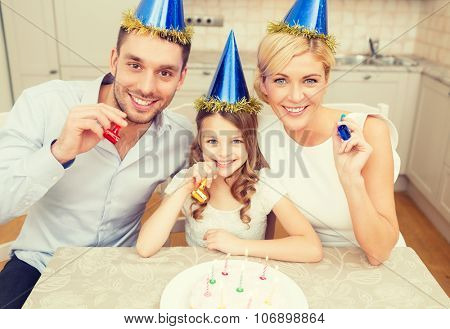 celebration, family, holidays and birthday concept - happy family in blue hats with cake and candles blowing favor horns