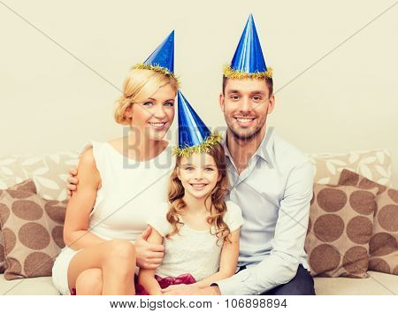 celebration, family, holidays and birthday concept - happy family in blue hats celebrating