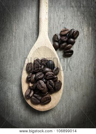 Fine roasted coffee beans on wooden spoon