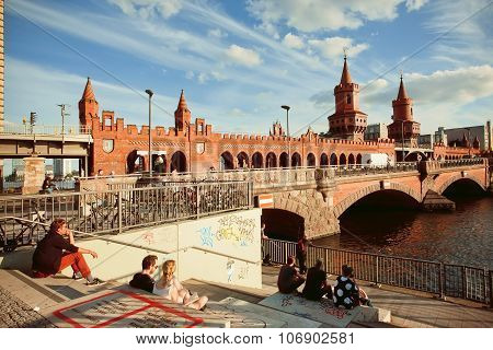 People Sitting At Riverbank Near 18Th Century Oberbaum Bridge