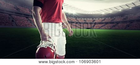American football player holding his helmet against rugby stadium